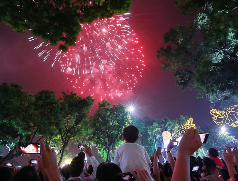 People watch the live fireworks in Hanoi on New Year Eve